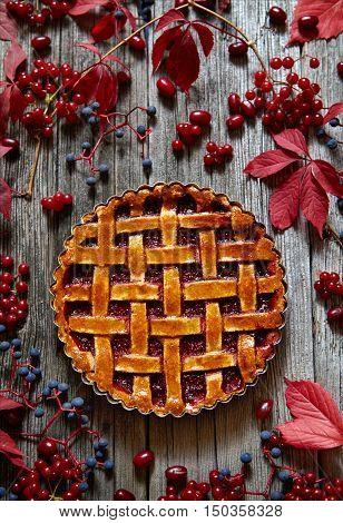 Homemade Thanksgiving traditional sweet raspberry tart pie with jam on vintage wooden table background. Autumn creative composition decoration. Rustic style and natural light.