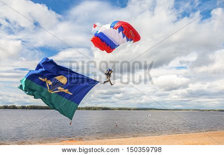 SAMARA RUSSIA - SEPTEMBER 11 2016: Single military parachute jumper on a wing parachute execute a controlled descent by parachute hung with airborne flag