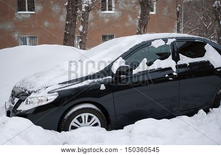 Black car covered with snow standing in snow near the house. Winter picture.
