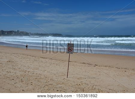 Sydney, Australia - Jan 29, 2013. A sign reads beach closed. No swimming flag on the beach before/after storm.