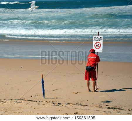 Sydney, Australia - Jan 29, 2013. A sign reads beach closed. No swimming flag on the beach before/after storm.Lifeguard at the sign.