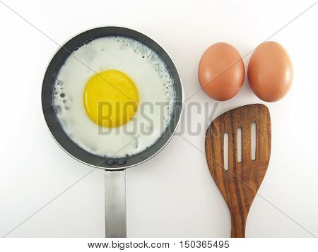 Fried egg in pan, two eggs and spatula on a white background, top view preparing breakfast