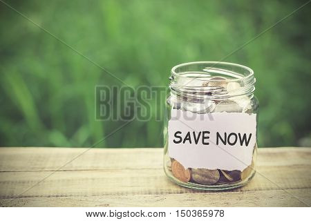 Money in the jar on wooden table with filter effect retro vintage style. Money and business concept