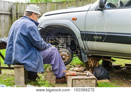 The mechanic is repairing the front hub wheels. car repair at home.