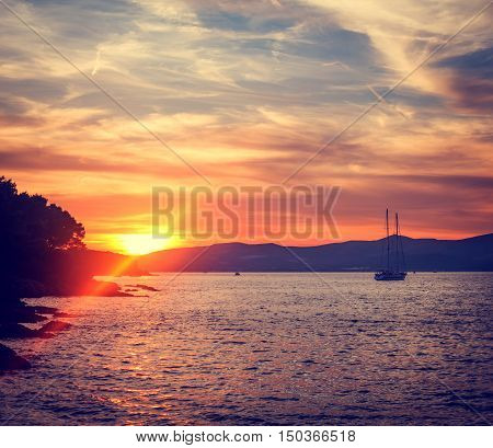 Beautiful Seascape with Silhouette of Sailing Yacht in Calm Bay at Sunset. Quiet Sea. Artistic Lens Flare Effect. Toned and Filtered Photo with Copy Space.