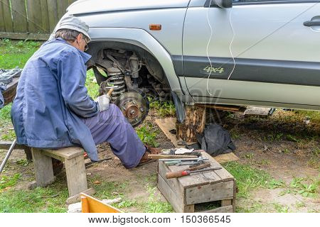 Senior mechanic repairing the front hub wheels. vehicle repair in the absence of the service station.