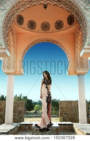 Beautiful Fashion Brunette Woman In Elegant Dress With Long Wavy Hair Style Posing Under Ornamental