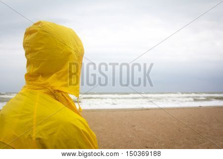 Men in yellow raincoat on the beach looking at storm. Man on the edge of the world concept