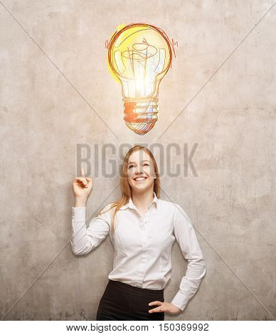 Portrait of smiling blond businesswoman pointing at large light bulb sketch on concrete wall above her head. Concept of new idea. Toned image