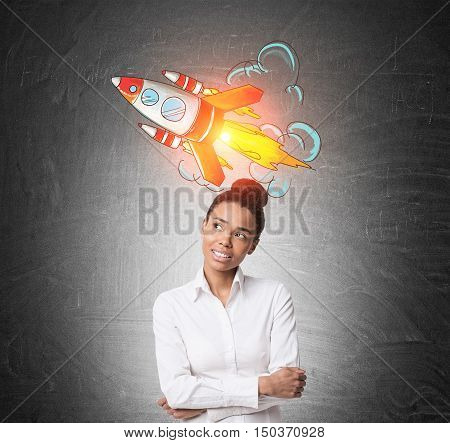 Portrait of thinking African American girl with flying rocket sketch on blackboard. Concept of project launching.