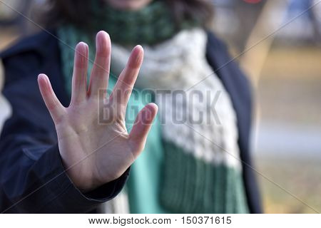 Woman put forth a hand in stopping gesture close-up