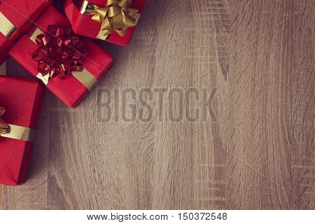 Several nicely wrapped present boxes with ribbons set on a coffee table as a background. Focus on the presents