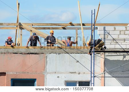 LYAKHOVICHI, BELARUS - AUGUST 28, 2016: A team of builders assembles scaffolding for construction work