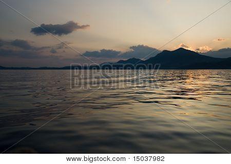 paisaje con mar y montaña en puesta de sol