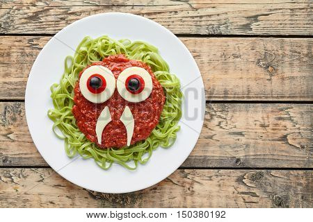Funny creative halloween food monster green spaghetti pasta with fake blood tomato sauce and mozzarella eyeballs holiday decoration kid party meal on vintage wooden table background.