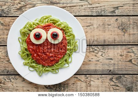 Green spaghetti pasta creative halloween food monster with fake blood tomato sauce and big mozzarella eyeballs holiday decoration kid party meal on vintage wooden table background.