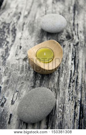 nature driftwood wood background with handmade candle with gray stone,