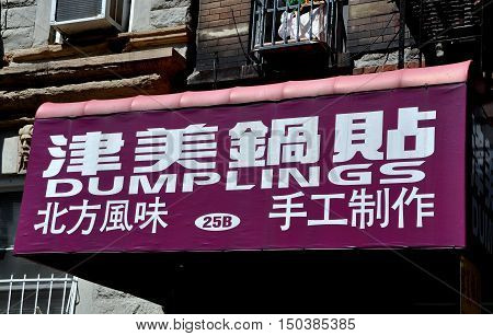 New York City - August 29 2012: Sign in both English and Chinese advertises handmade northern China style dumplings at a Henry Street restaurant in Chinatown