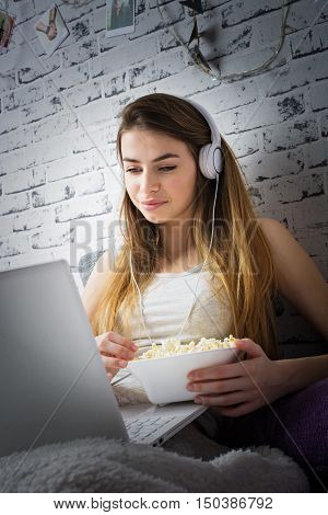 Young blonde teenage woman at home in bed watching movie on laptop, eating popcorn, with headphones on, smiling. Brick wall background.