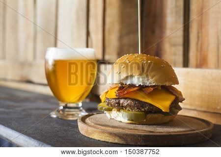Tasty hamburger with a glass of beer on wooden counter. Pickles bacon and cheddar cheese