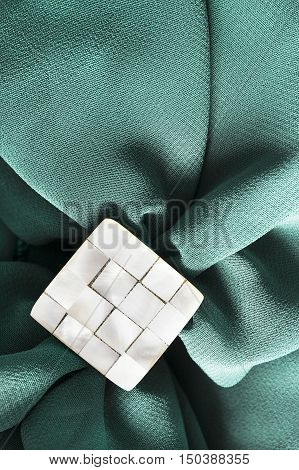 Nacre brooch on crumpled blue silk as a background