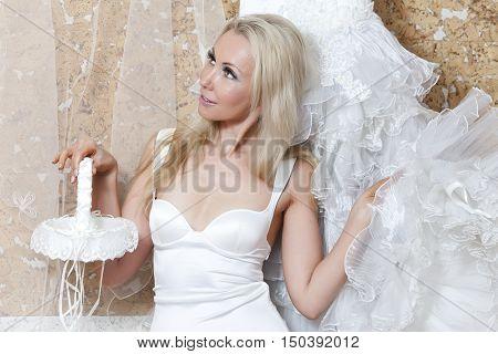 The beautiful woman, the bride near wedding dress dreams about wedding