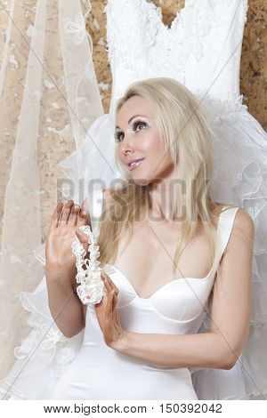 The bride the young woman with blonde long hair with a garter in hands dreams of a wedding near a wedding dress