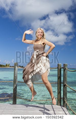 the beautiful woman jumps up on a wooden platform over the sea