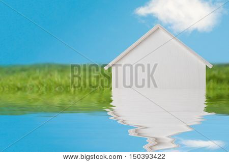 Conceptual photograph of a white wooden house in bright green grassy landscape with blue sky appearing to sink into a flood of water. Water has been added artificially.