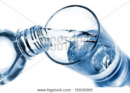 water pouring into glass from bottle isolated on white