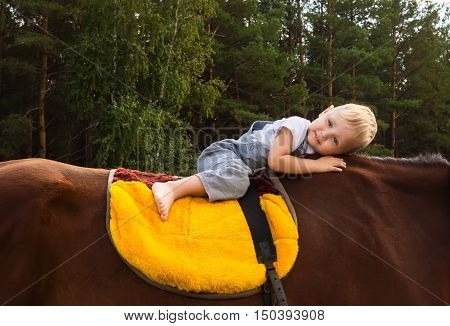 Happy barefooted baby 3 years old riding on horse without a saddle