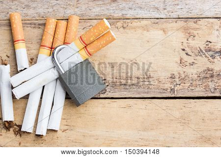 Tobacco cigarettes with lock on a wooden table background. cigarette with health concept
