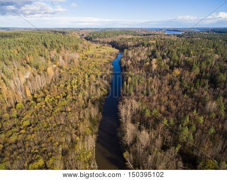 Beautiful aerial view of a small river in the forest. The Republic of Karelia. Further, one can see meadows and fields. On the sky clouds float. Russia, 2016