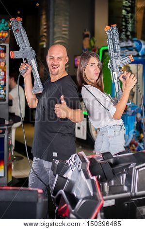 Young Couple Posing With A Toy Shotgun