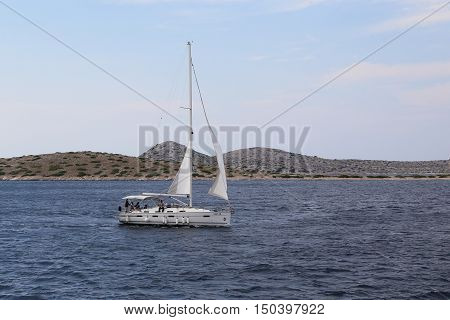 NATIONAL PARK KORNATI, CROATIA - SEPTEMBER 7, 2016: Yacht is sailing in the Kornati archipelago which is a favorite destination for lovers of sailing.