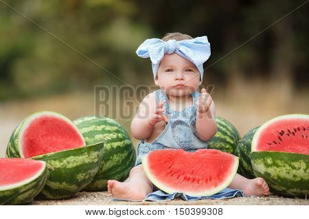 Little cheerful girl with gray eyes,in blue denim overalls and a blue bandana on his head tied with a bow,sitting on the ground in the garden next to the large cut, ripe red, juicy watermelons