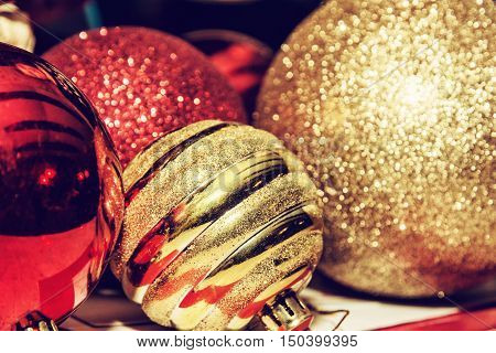 Red and yellow shimmering christmas baubles. Symbolic objects. Retro photo filter. Xmas decoration.