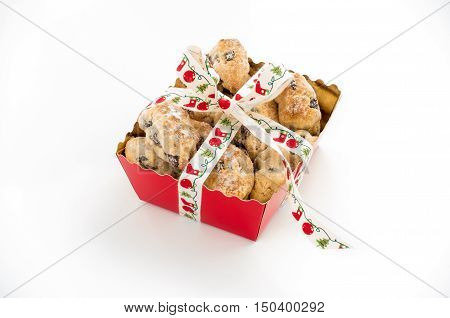 Mini Christstollen in a festive red tray decorated with ribbon isolated on white background.