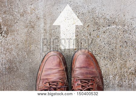 Male feet in old brown leather shoes stand on asphalt pavement with white arrows pedestrian crossing road marking