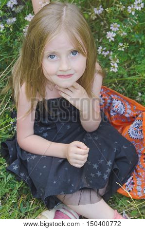 Portrait of a little girl in a summer meadow with decorations of field flowers
