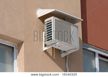 Air Conditioning Heat Pump Mounted On Brick Wall.
