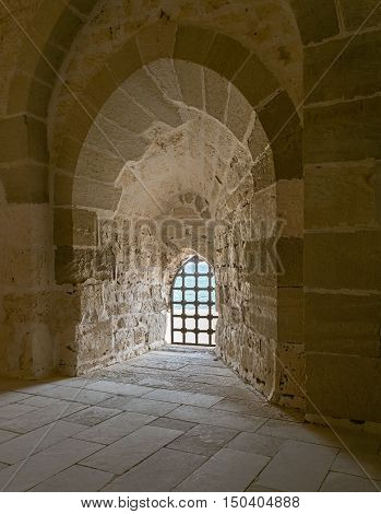 Stone wall with one backlit window with iron grid at one of the passages of Alexandria Citadel Egypt. A fifteenth century defensive fortress by the Mediterranean sea coast