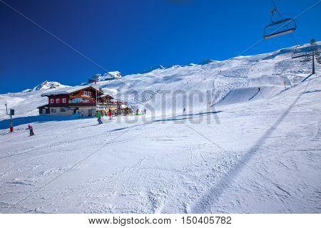 HOCH-YBRIG, SWITZERLAND, February 2015: Skiers skiing on ski slopes near Alperestaurant Staefel on the top of Hoch Ybrig resort Switzerland