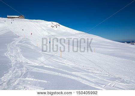 Skiers skiing on ski slopes on the top of Hoch Ybrig resort in Swiss Alps, Central Switzerland