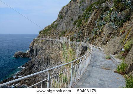 Rocky sea shore and way of love (via dell'amore) in Riomaggiore in Liguria Italy. One of five Cinque Terre cities (unesco world heritage)