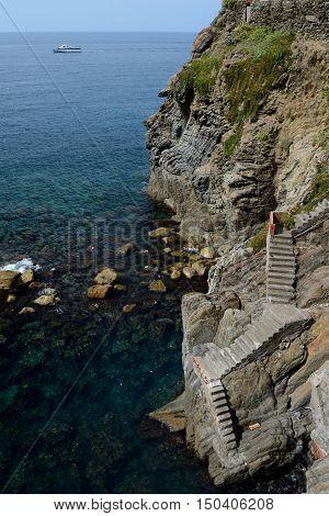 Concrete stairs on rocks to the sea in Riomaggiore in Liguria Italy. One of five Cinque Terre cities (unesco world heritage)