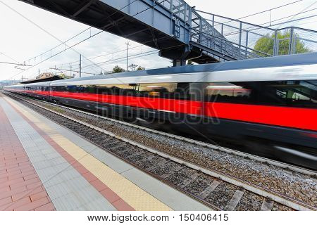 High speed passenger trains on railroad platform in motion. Blur effect of commuter train. Railway station in Florence Italy. Industrial landscape