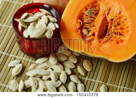 dried pumpkin seeds are snacks that  healthy. dried pumpkin seeds with fresh pumpkin on Bamboo mat background