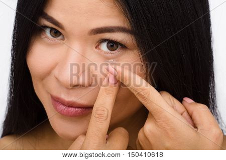 Closeup of woman putting contact lenses over white background. Lady putting lenses and looking at camera.