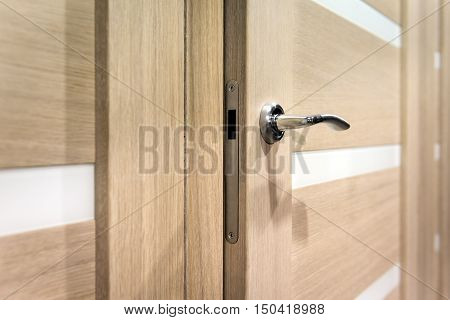 Part of wooden open door with silver door-handle